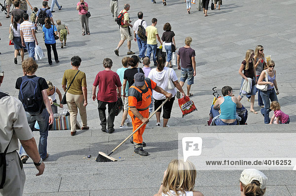 Street sweeper with broom  street cleaning  pedestrians  Domplatz  Cathedral Square in Cologne  North Rhine-Westphalia  Germany  Europe