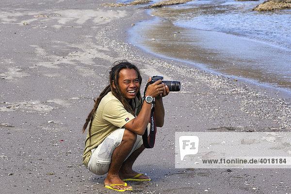 Divemaster Santoso of MS-Felicia taking pictures on the beach  Komodo National Park  World Heritage Site  Komodo  Indonesia  Asia