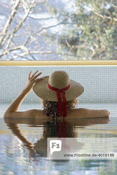 Frau am Beckenrand des Pools