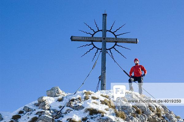 Eine Frau  22  am Gipfelkreuz des Steinernen Jäger in den Voralpen bei Reichraming im Winter  Oberösterreich  Österreich  Europa