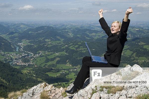 Geschäftsfrau am Gipfel mit einem Laptop