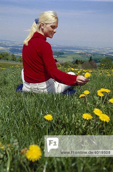 Blonde Frau mit rotem Pulli sitzt in der Wiese und pflückt eine Blume