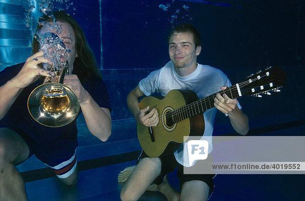 Musikanten spielen unter Wasser Trompete und Gitarre
