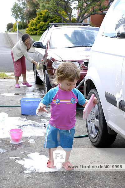 Zweijähriges Mädchen hat Spass daran  ihrer Mutter beim Waschen der Familienautos zu helfen