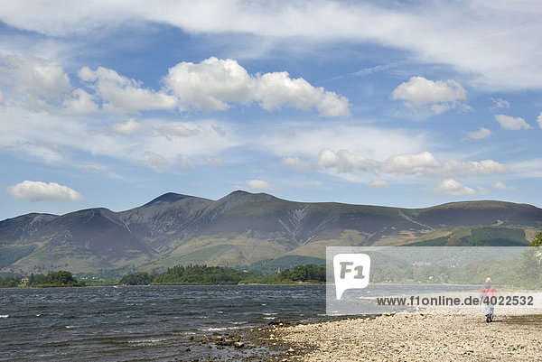 Woman at the lake's edge in front of a ridge of hills  Derwent Water  Derwentwater  Lake District  Cumbria  North England  Great Britain  Europe