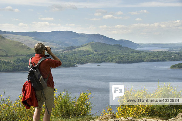 Hiker looking through field glasses at the lookout point  Surprise View  over Derwent Water in the Lake District  Cumbria  North England  Great Britain  Europe