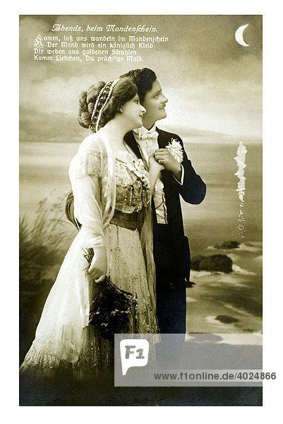 Valentin Grusskarte Mondschein-Romantik am Meer  Liebespaar in Umarmung in einer Mondnacht am Strand  Abends beim Mondenschein  Komm lass uns wandeln im Mondenschein  der Mond wird ein königlich Kleid Dir weben aus goldenen Strahlen  Komm Liebchen Dur prächtige Mais