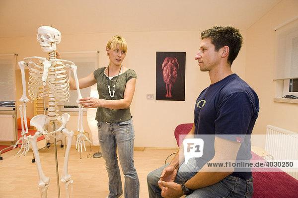 Physiotherapeutin  Lehrerin für Alexandertechnik gibt einem Patienten Erklärungen zu Anatomie mithilfe eines künstlichen Skeletts