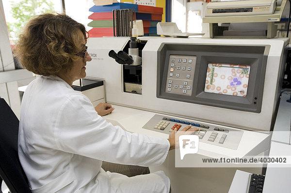 Laborantin in der Hämatologie bei der Differenzierung von Blut-Ausstrichen am Halbautomaten