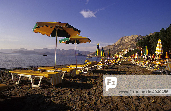 Sunshades  sun loungers  beach of Myrties  in the West of Kalymnos Island  Greece  Europe