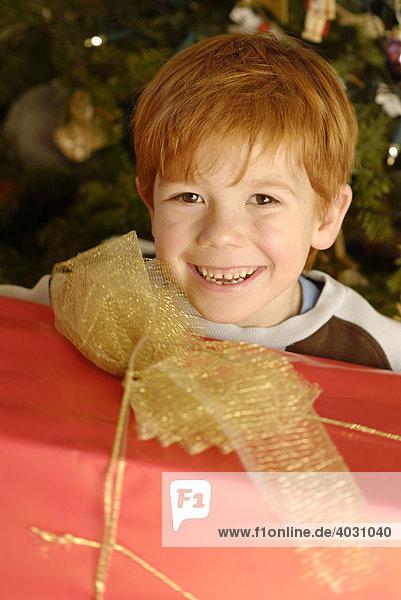 Kind mit einem großen Geschenk vor dem Weihnachtsbaum an Heiligabend