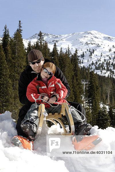 Vater mit seiner Tochter beim Schlittenfahren