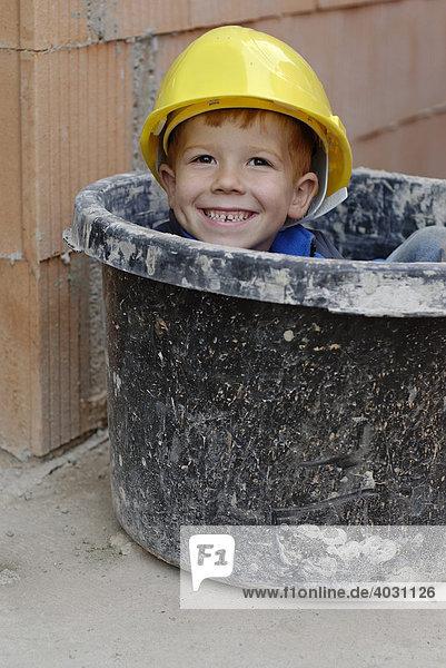 Kleiner Junge mit Bauhelm sitzt lächelnd in einem Mörtelkübel  Baukübel  in einem Rohbau auf einer Baustelle
