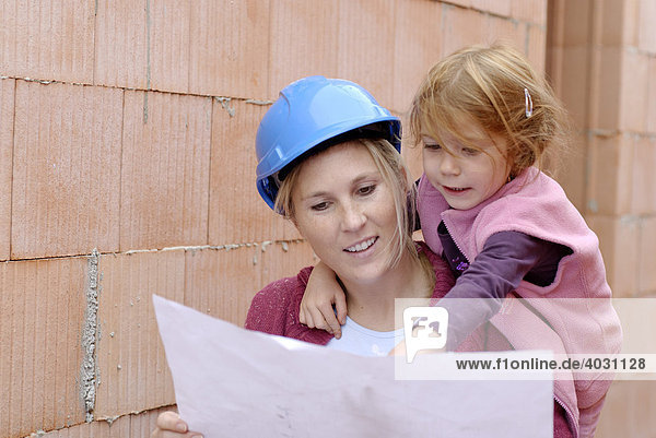 Mutter mit Bauhelm und Kind studieren Bauplan in einem Rohbau auf einer Baustelle