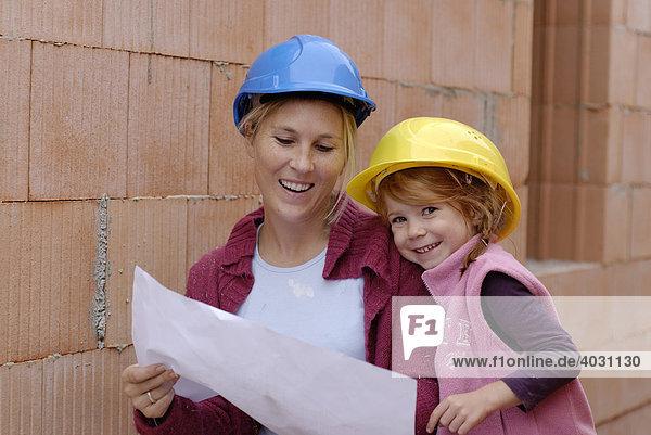 Mutter und Kind mit Bauhelmen studieren Bauplan in einem Rohbau auf einer Baustelle