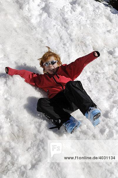 Kind rutscht auf einem schneebedeckten Hügel herunter spielt im Schnee