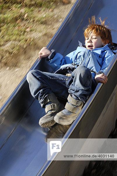 Kind auf einer Rutsche am Spielplatz
