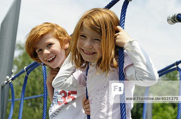 Kinder turnen auf einem Spielplatz im Klettergerüst