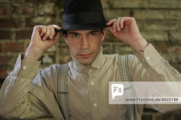 Portrait eines jungen Mannes im Stil der 20er Jahre mit Hut  Hemd  Hosenträgern