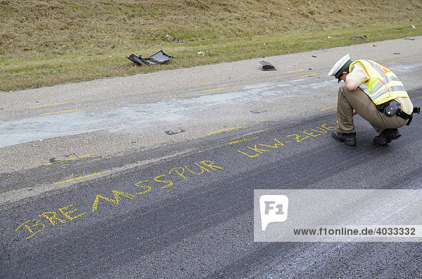 Young policewoman marking the road with crayon for accident expert after a road accident on a freeway  skidmark truck - witness  Altingen  Baden-Wuerttemberg  Germany  Europe