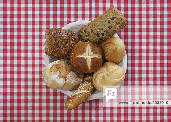 Brot  Brotkorb gefüllt mit verschiedenen Brötchen auf rot weiß karierter Tischdecke