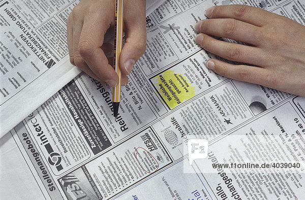 Job search  hand marking job advertisements for cleaning help with a pen  newspaper