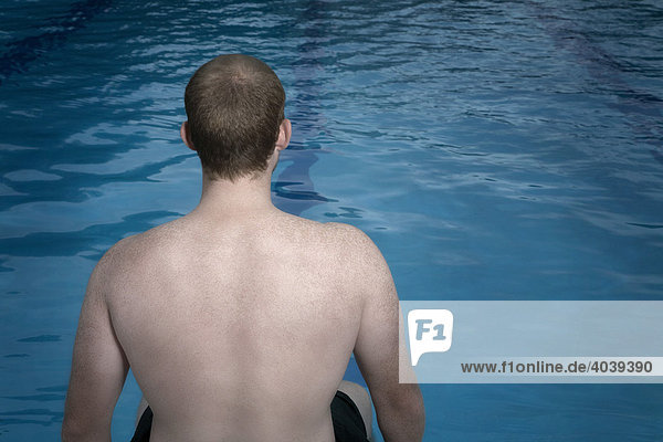 Young man sitting on the edge of a swimming pool