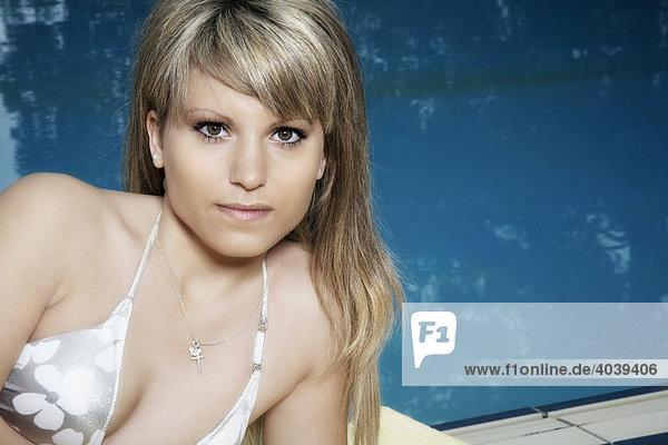 Young dark-blond woman wearing a bikini at a swimming pool