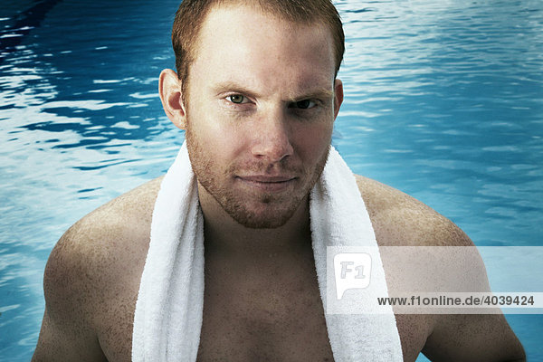 Young man with towel over his shoulders by the swimming pool