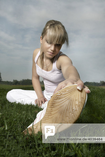 Young dark blonde woman stretching
