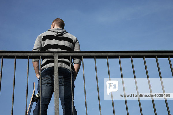 Young man with a skateboard on a railing