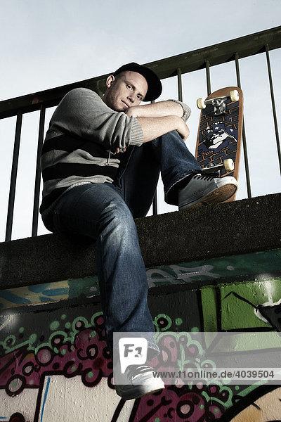 Junger Mann sitzt mit seinem Skateboard auf einer mit Graffiti besprühten Wand