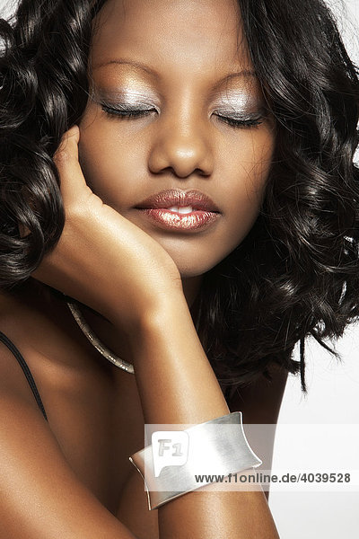 Portrait of a young dark-skinned woman with her eyes closed  hand on cheek