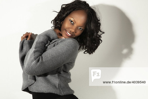 Portrait of a smiling young dark-skinned woman wearing a grey knitwear top