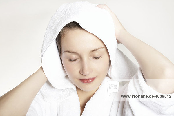 Young brunette woman drying her hair