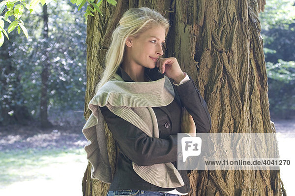 Model wearing a scarf leaning against a tree
