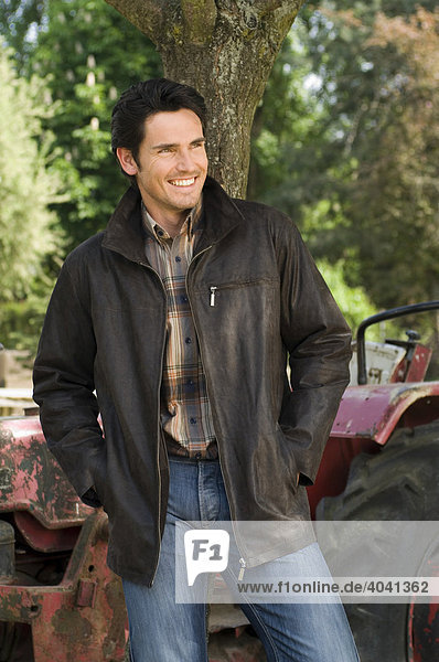 Man wearing an outdoor jacket in front of a tractor
