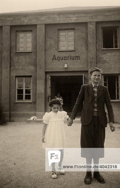 Historical photo  girl and boy in front of an aquarium  1949