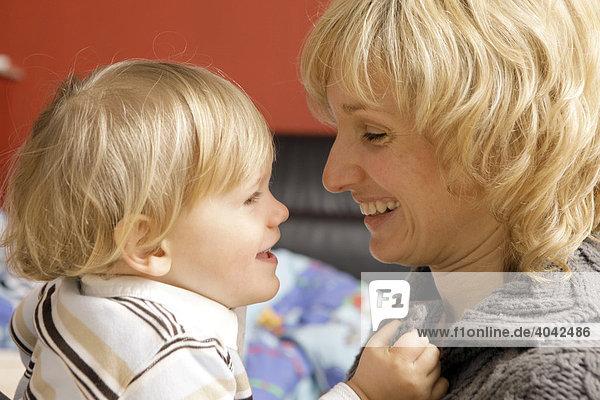 Blonde Mutter lacht mit 2-jährigem Jungen