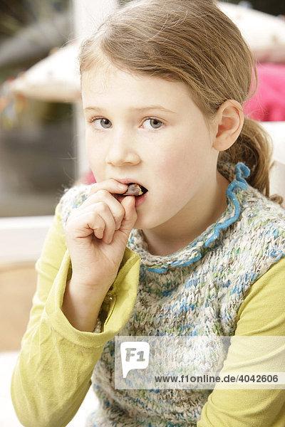 8-jähriges Mädchen isst Schokolade  mit schlechtem Gewissen