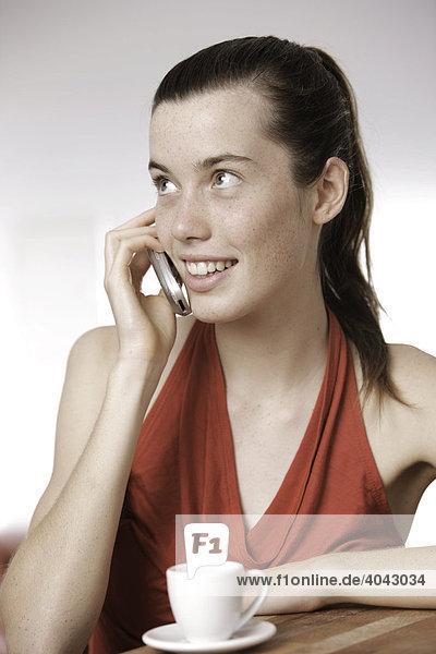 17-jähriges Mädchen im roten Kleid mit Handy und Espresso