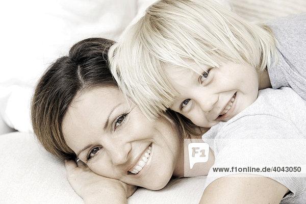 Blonder Sohn und Mutter liegen auf dem Sofa