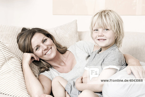 Mother and son on a couch  smiling