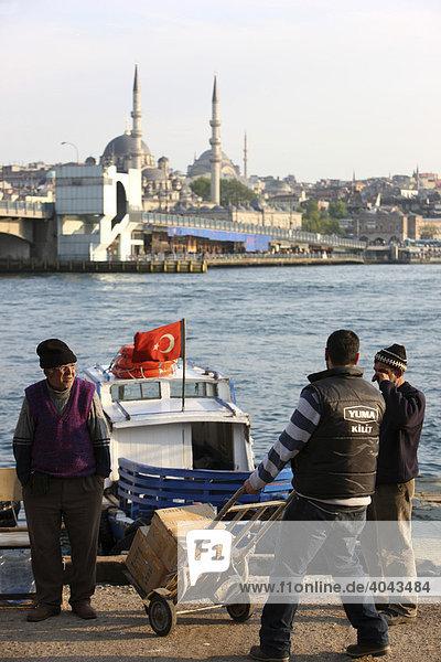 Männer beim Beladen  türkische Flagge  kleine Flußfähre  Bootstaxi am Goldenen Horn  neben der Galatabrücke  Istanbul  Türkei