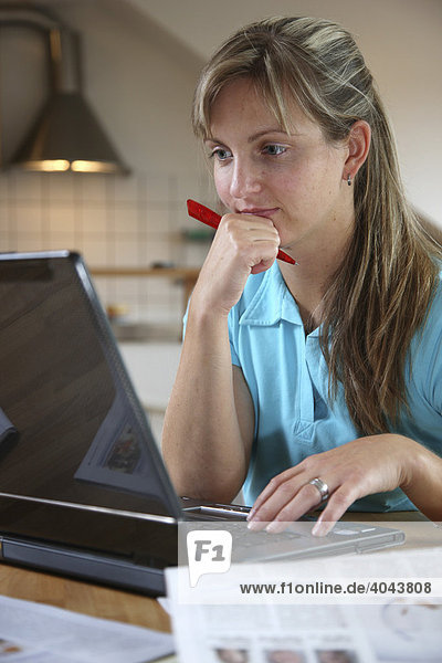 Junge Frau  25-30 Jahre  surft im Internet mit Laptop Computer am Küchentisch