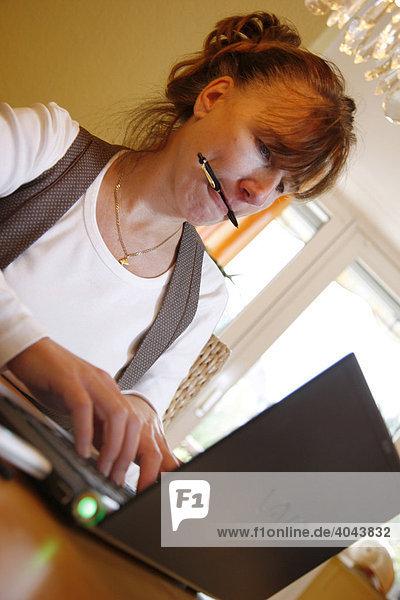 Frau  45 Jahre  surft im Internet mit Laptop Computer  DSL Stick  mobiles Internet  am Esstisch