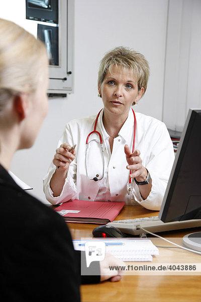 Ärztin spricht mit einer Patientin im Arztzimmer in einem Krankenhaus
