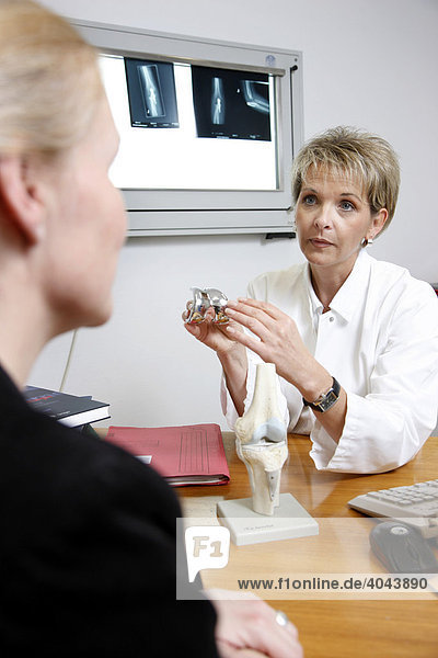 Ärztin spricht mit einer Patientin im Arztzimmer in einem Krankenhaus  Beratung vor einer Knieoperation anhand eines Models