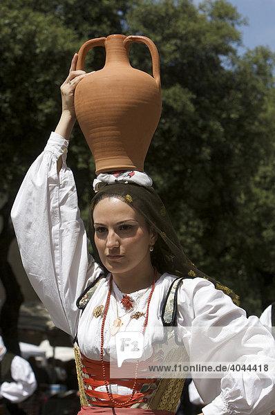 Junge Frau mit Amphore auf dem Kopf in traditionellem Kostüm auf der Cavalcata Sarda in Sassari  Sardinien  Italien  Europa
