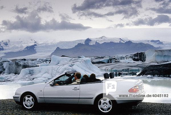 Pärchen sitzt in einem silbernen Mercedes Cabriolet mit offenem Verdeck vor einem Gletschersee  Jökulsárlón am Fuße des Vatnajökull  Island  Europa